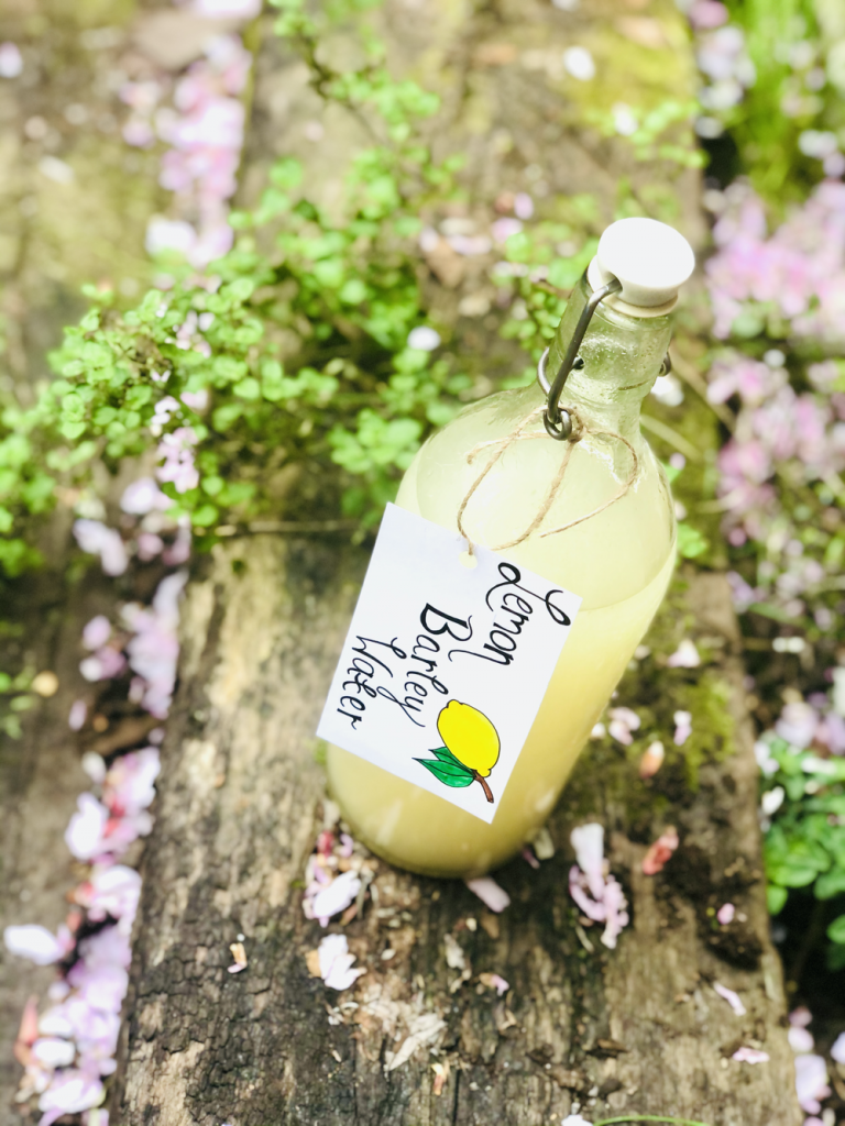 bottle of homemade lemon barley water stood on a wooden railway girder with herbs and blossoms in the background