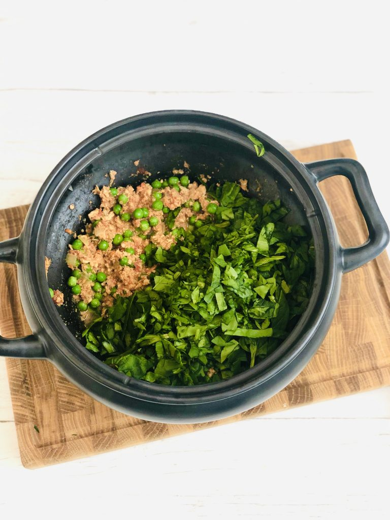 wooden board with slow cooker pan on it - pan filled with slow cooker turkey keema curry that's cooked through - 2 handfuls of frozen peas stirred through, 4 handfuls of spinach have just been added