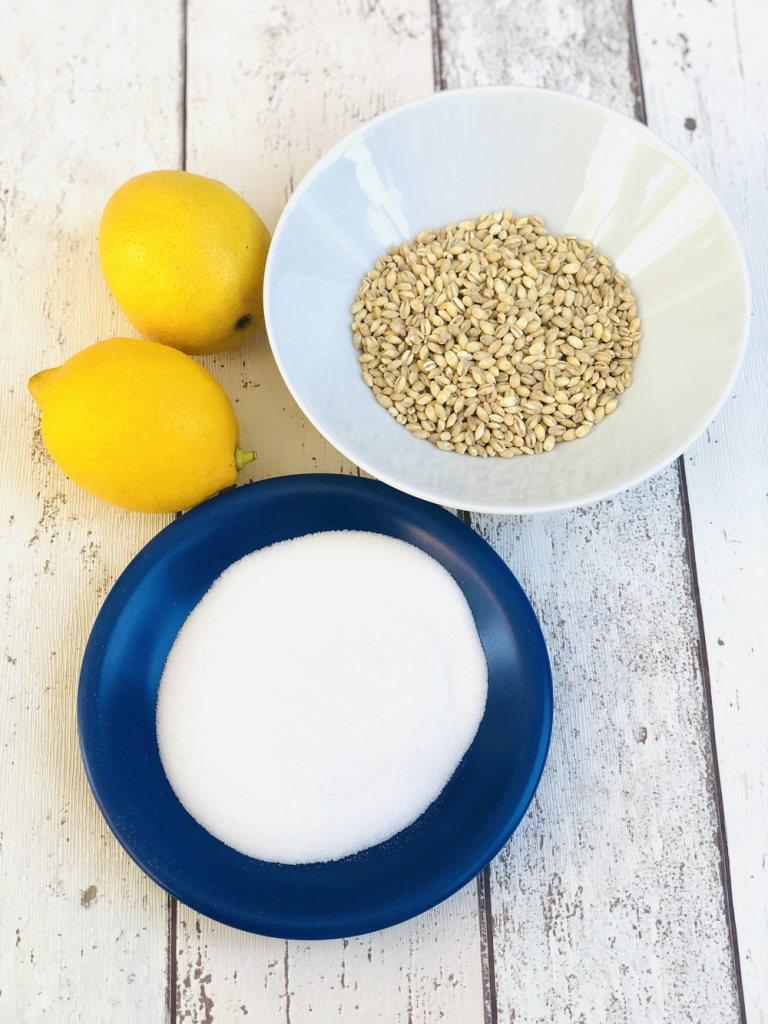 ingredients for lemon barley water - sugar on a blue plate, bowl of barley, two lemons