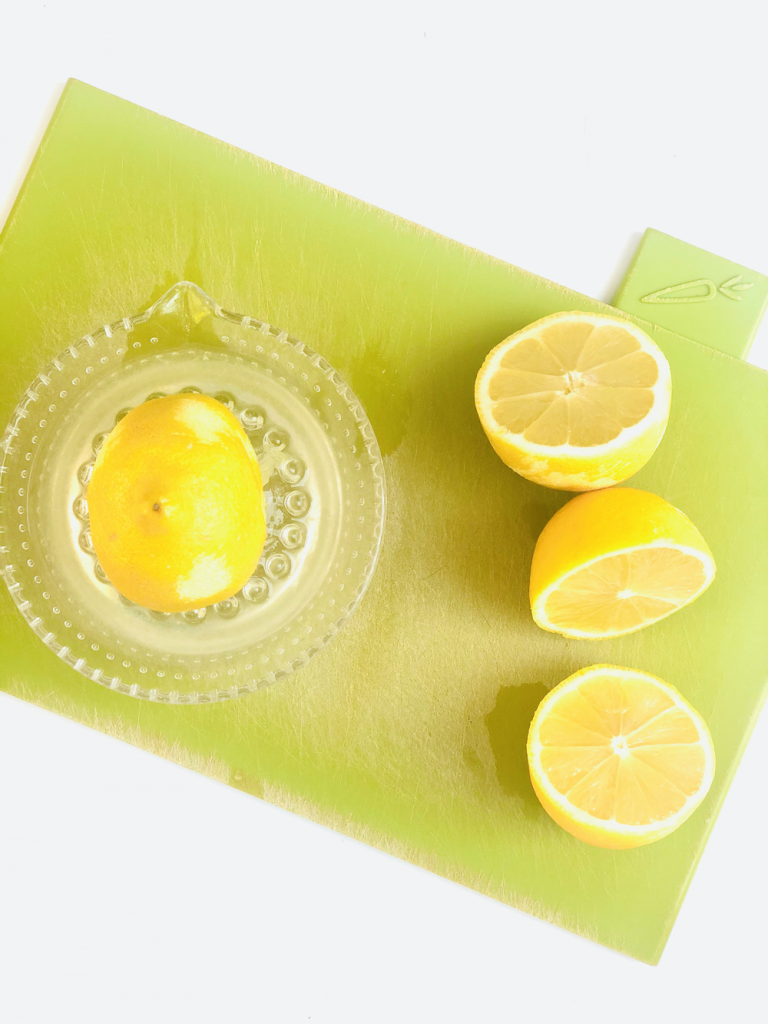 lemons being juiced on a glass lemon squeezer