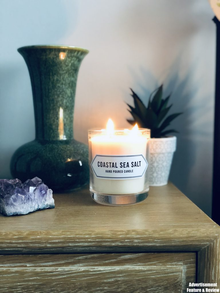 Norfolk Natural Living Coastal sea salt scented candle - stood by a plant, a green vase and amethyst crystal