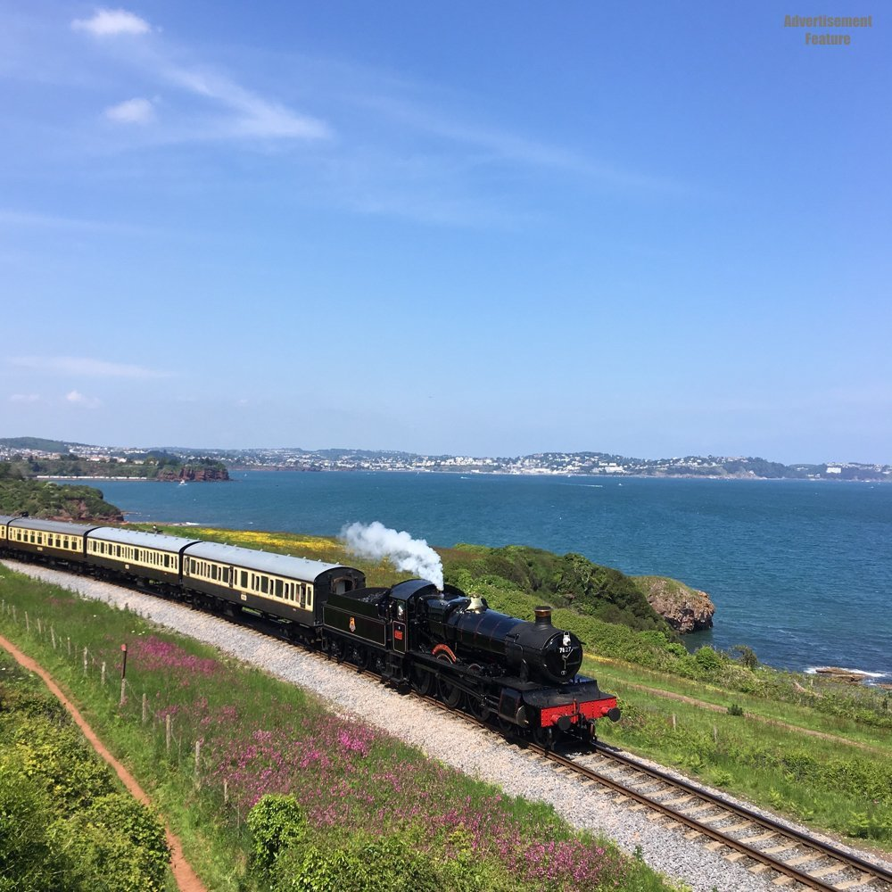 Steam train puffing along the tracks with the Torbay sea in the background
