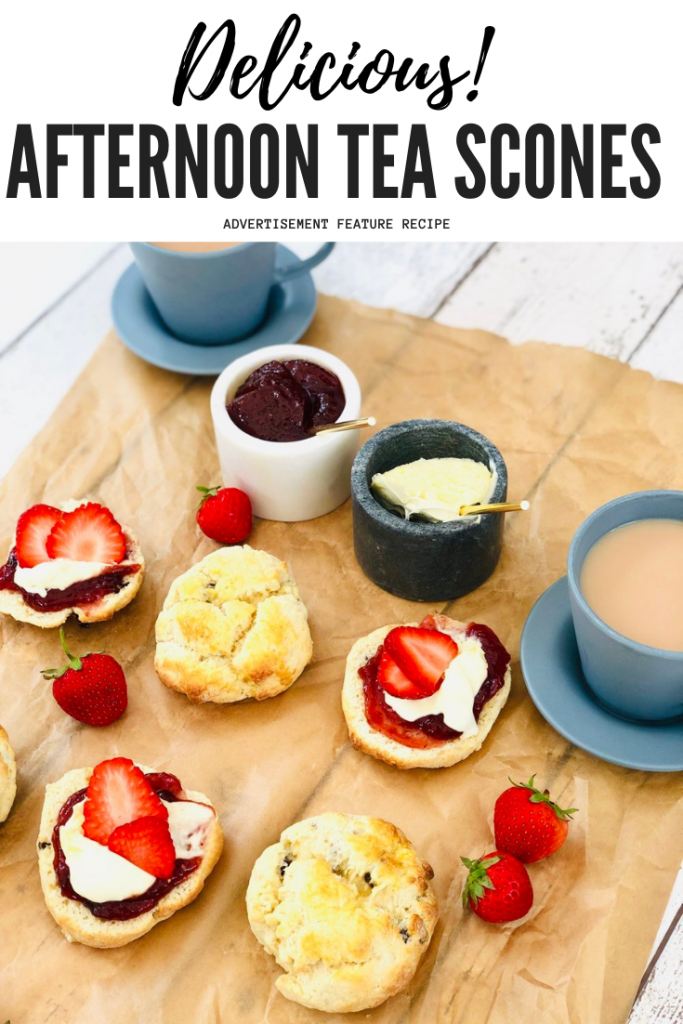 """afternoon tea scones topped with clotted cream and strawberry jam, cups of tea in small blue cups and fresh strawberries are on the table. Text overlay reads """"delicious afternoon tea scones"""""""