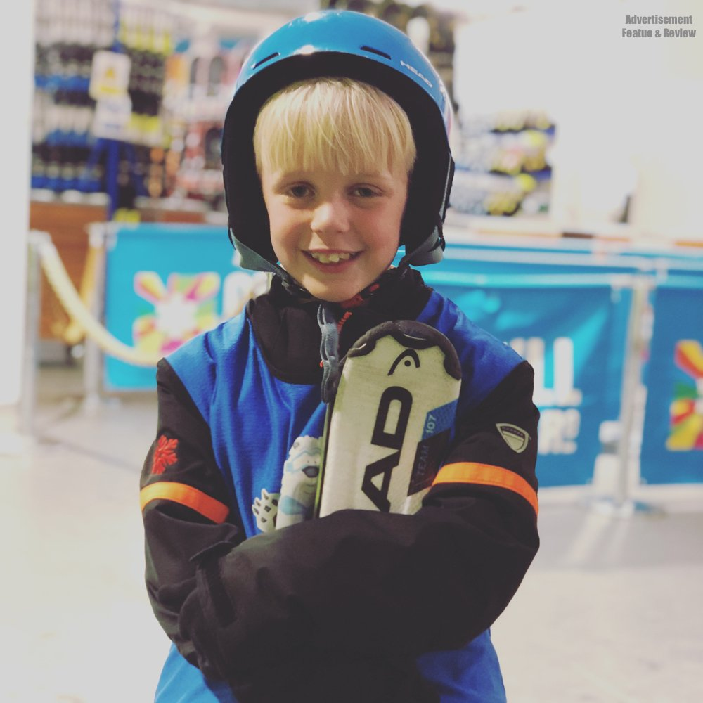 Young boy in ski gear holding skies at Chillfactore ready for kids ski lessons