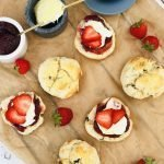 platter of homemade scones with strawberry jam and clotted cream.
