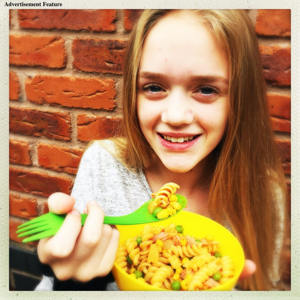 girl eating lunchbox pasta salad from a yellow bowl with a green spork