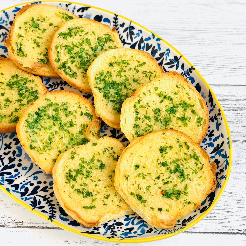 homemade brioche garlic bread slices on a blue, white and yellow platter