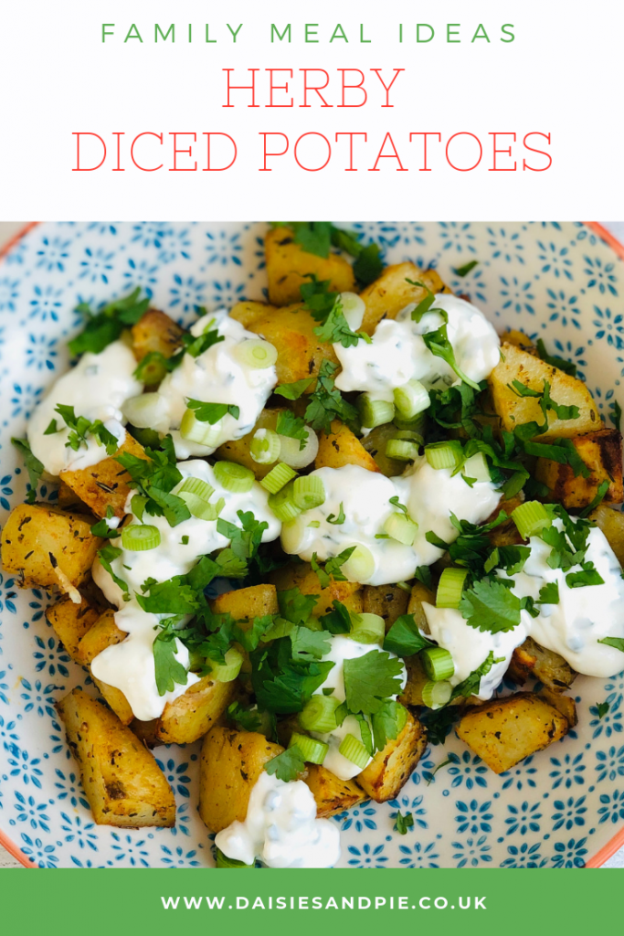 """homemade herby diced potatoes with soured cream, spring onions and freshly chopped herbs. Text """"family meal ideas - herby diced potatoes"""""""