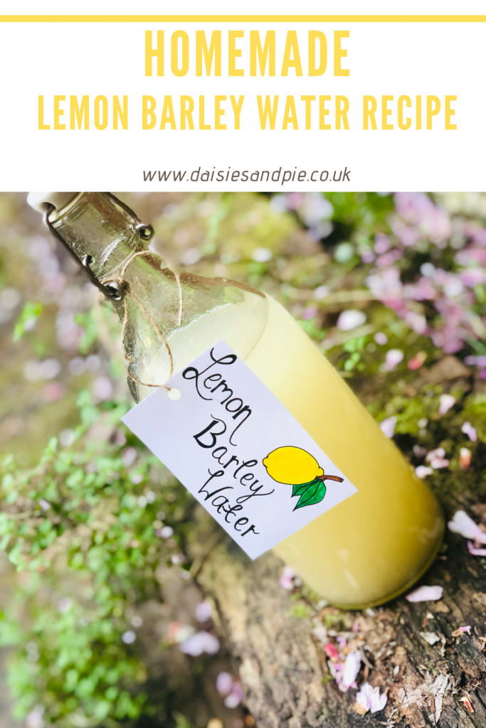 "bottle of homemade lemon barley water stood on a wooden railway girder with herbs and blossoms in the background . Text ""homemade lemon barley water recipe - www.daisiesandpie.co.uk"""