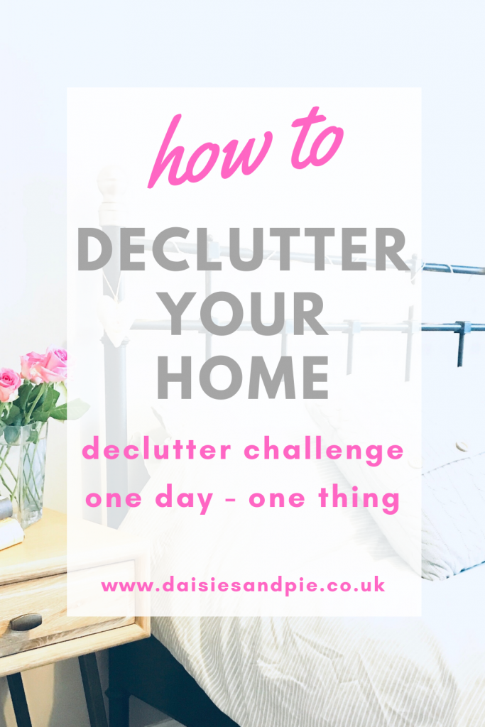"pale grey bed with a wooden bedside table with neat stack of books and vase of pink roses. text ""how to declutter your home - declutter challenge - one day - one thing"""