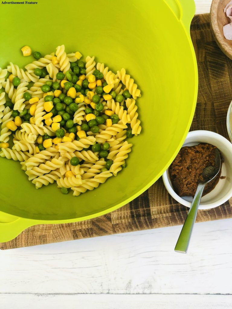 bright green joseph joseph mixing bowl filled with cooked fusilli pasta, peas and sweetcorn with small white bowl of sun dried tomato pesto next to the bowl