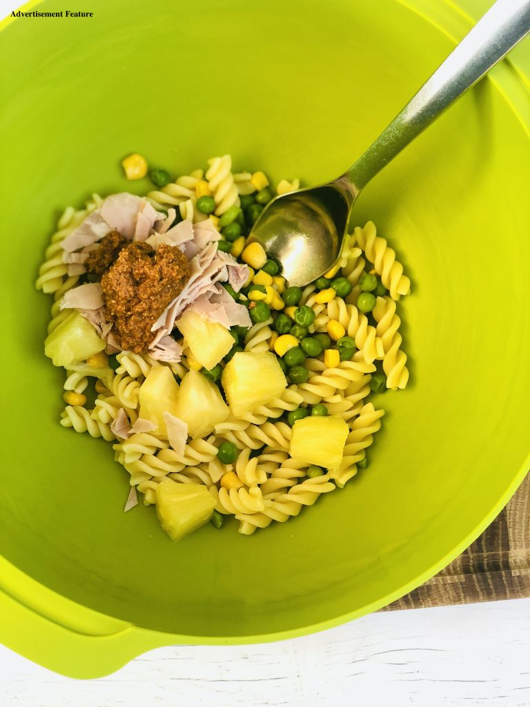 bright green joseph joseph mixing bowl filled with cooked fusilli pasta, peas, sweetcorn, pineapple cubes, chopped ham and a spoonful of sun dried tomato pesto