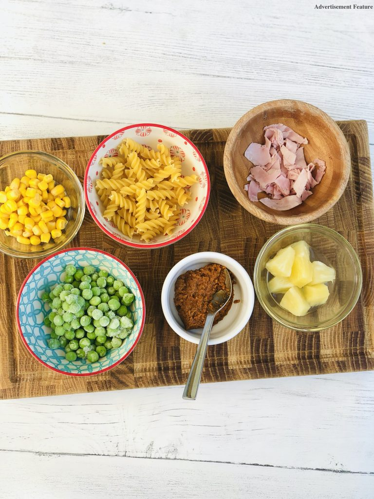 ingredients for lunchbox pasta salad in small bowls on a wooden chopping board - sweetcorn, frozen peas, fusilli pasta, sun dried tomato pesto, chopped ham, pineapple cubes