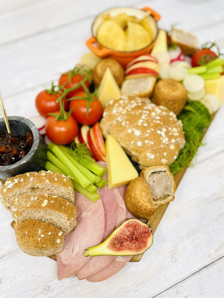 ploughman's lunch platter with bread, cheese, pork pies, chutney, fruit and salad