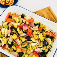 enamel roasting tin filled with roasted vegetables - roast veg includes red peppers, courgettes, fennel, red onions and aubergine