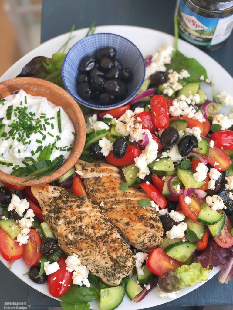 Greek salad with chicken - big platter of greek salad with seasoned chicken breasts, tzatziki dip, feta cheese and olives.