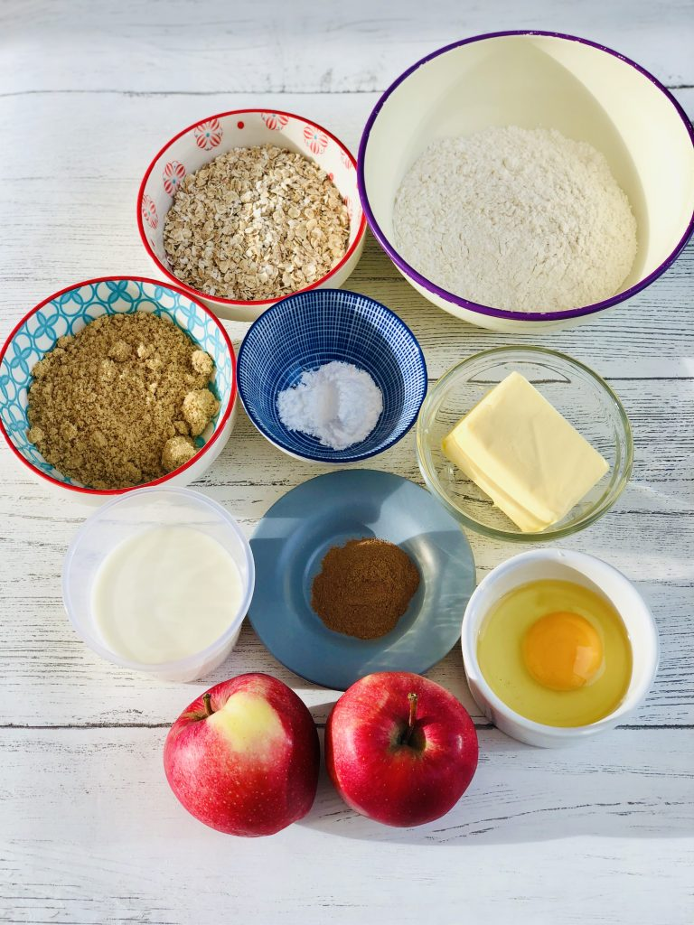 ingredients for apple and oat breakfast muffins gathered together in bowls on a white table - there is self raising flour, oats, brown sugar, baking powder, cinnamon, butter, milk, egg and two apples