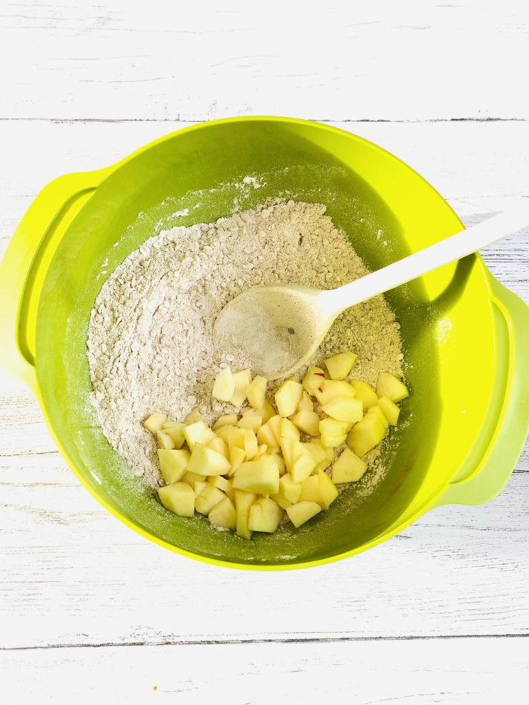 Joseph Joseph green mixing bowl filled with self raising flour, oats, baking powder, cinnamon, brown sugar all mixed together with a wooden spoon, chopped peeled apple tipped into the bowl ready to mix in to the dry ingredients
