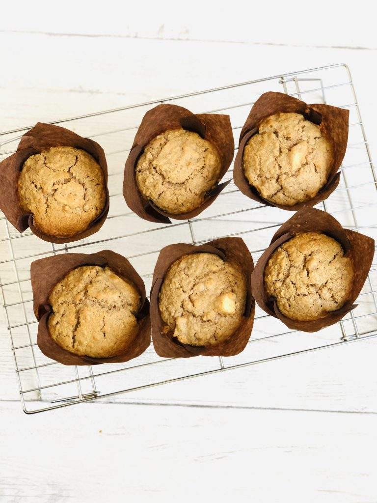 six freshly baked homemade apple and oat muffins in brown paper muffin cases cooling on a stainless steel cooling wrack on a white table top