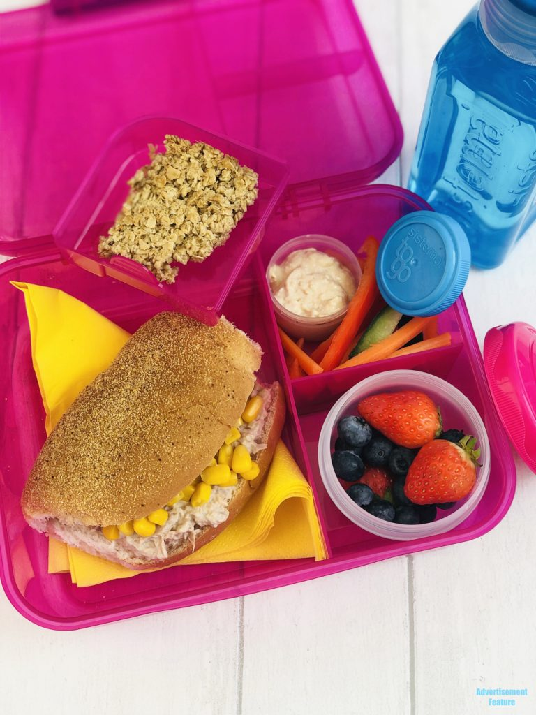 healthy packed lunch idea - tuna and sweetcorn roll, fresh fruit salad pot, hummus with veggie sticks, homemade flapjack, bottle of water - all packed in Sistema lunch boxes and pots