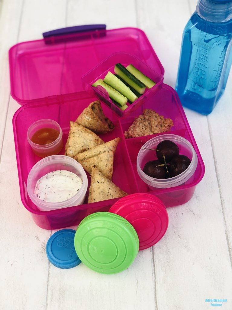 healthy packed lunch idea for kids - vegetarian samosas, minty yogurt dip, mango chutney dip, cucumber sticks, homemade flapjack, pot of cherries, bottle of water all packed in Sistema lunch boxes and pots.