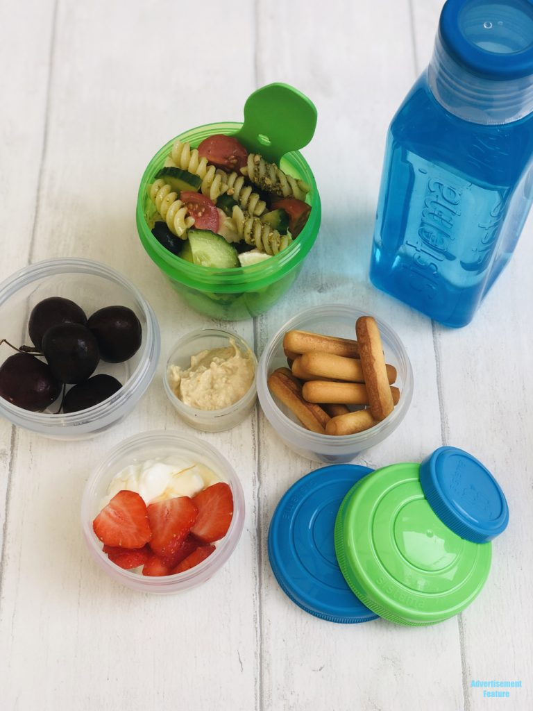 healthy packed lunch for kids - homemade pasta salad with mozzarella, pot of cherries, pot of hummus with breadsticks, pot of greek yogurt with strawberries and honey, bottle of water. All packed in Sistema lunch boxes and pots