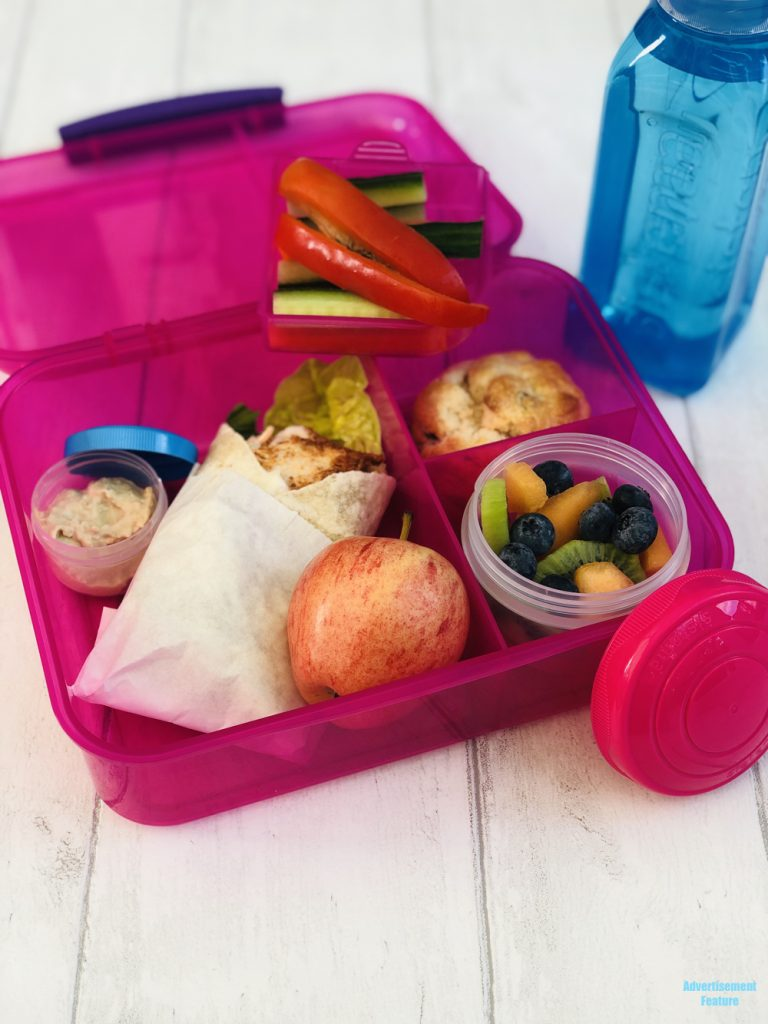healthy packed lunch idea for kids - BBQ chicken and salad wholemeal wrap, pot of hummus, veggie sticks, fresh fruit salad, homemade fruit scone, apple and bottle of water. All packed in Sistema lunch boxes and pots