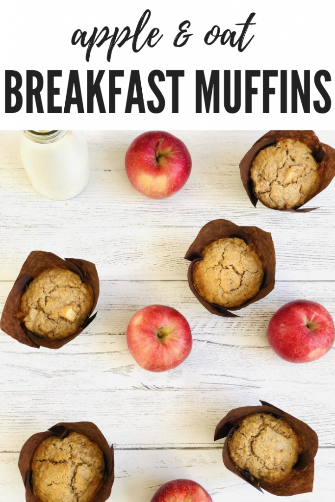 "freshly baked homemade apple and oat muffins in brown paper muffin cases on a white rustic table top with shiny red apples spaced in between the muffins, bottle of milk with bamboo straw alongside. Text overlay ""apple and oat breakfast muffins"""