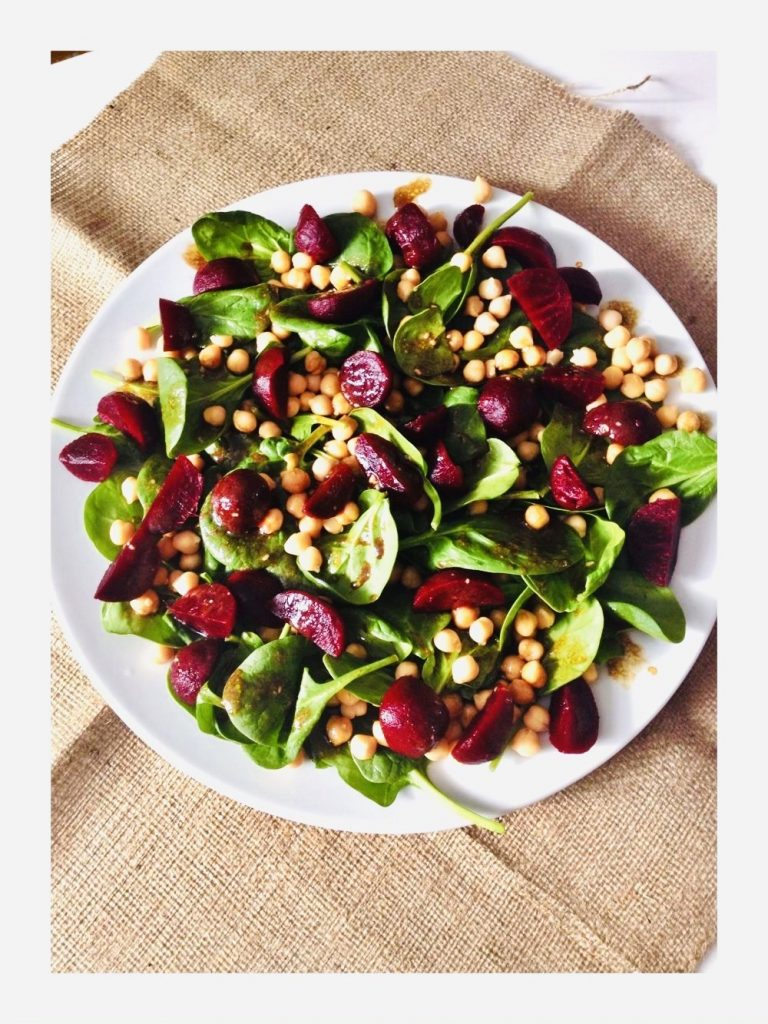 Beetroot Salad with chickpeas and spinach on a white plate on a hessian tablecloth