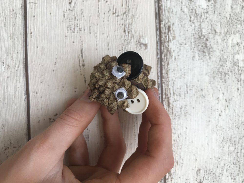 pine cone with button ears and two google eyes - being made into a pine cone mouse