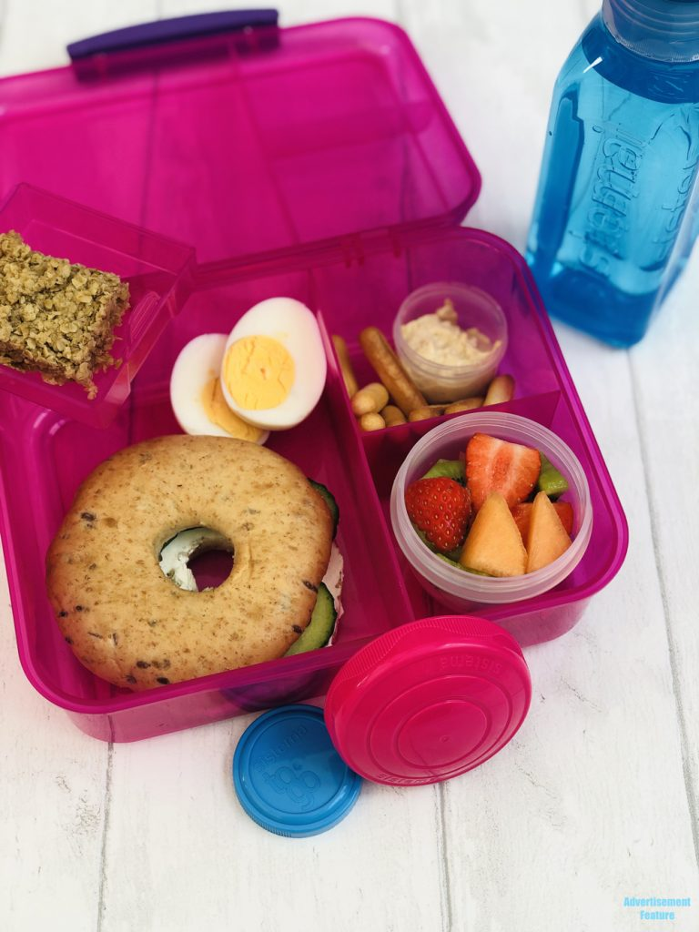 healthy packed lunch idea for kids - cream cheese and cucumber wholegrain bagel, boiled eggs, fresh fruit salad pot, hummus dip with breadsticks, homemade flapjack, bottle of water all packed in Sistema lunch boxes and pots.