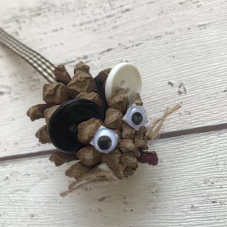 pine cone with button ears, google eyes, ribbon tale and string whiskers being made into a pine cone mouse