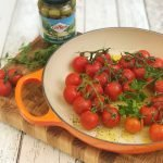 roasted baby vine tomatoes with fresh oregano in enamel pan
