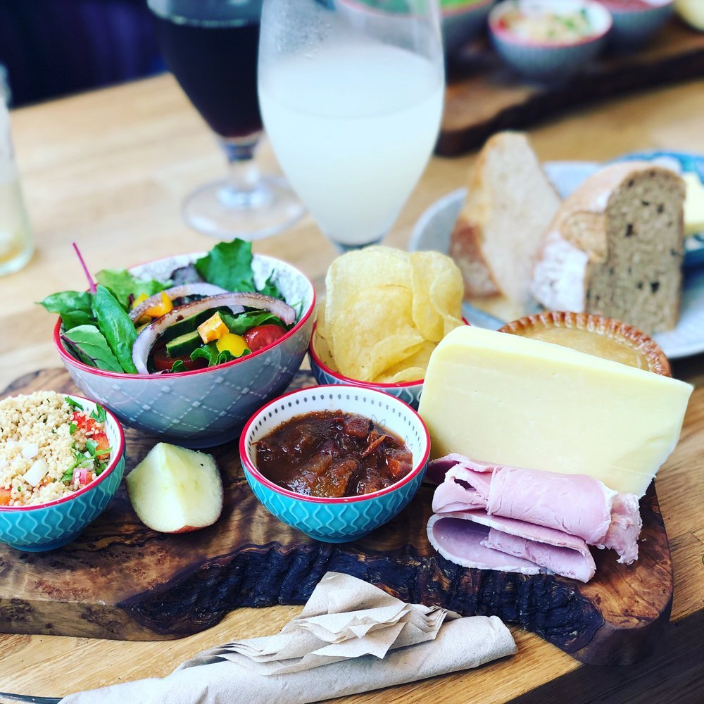 ploughman's platter from The Allotment coffee shop Wigan. served on wooden board - homegrown salad, couscous salad, Reedy's chutney, Leagrams lancashire cheese, fiddlers crisps, fresh artisan bread from All You Knead and pork pie