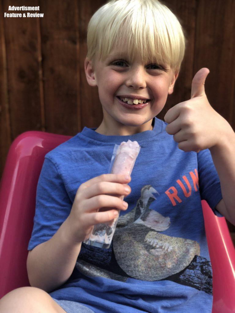 boy eating a yopop made in the YoPop frozen yogurt treat maker toy