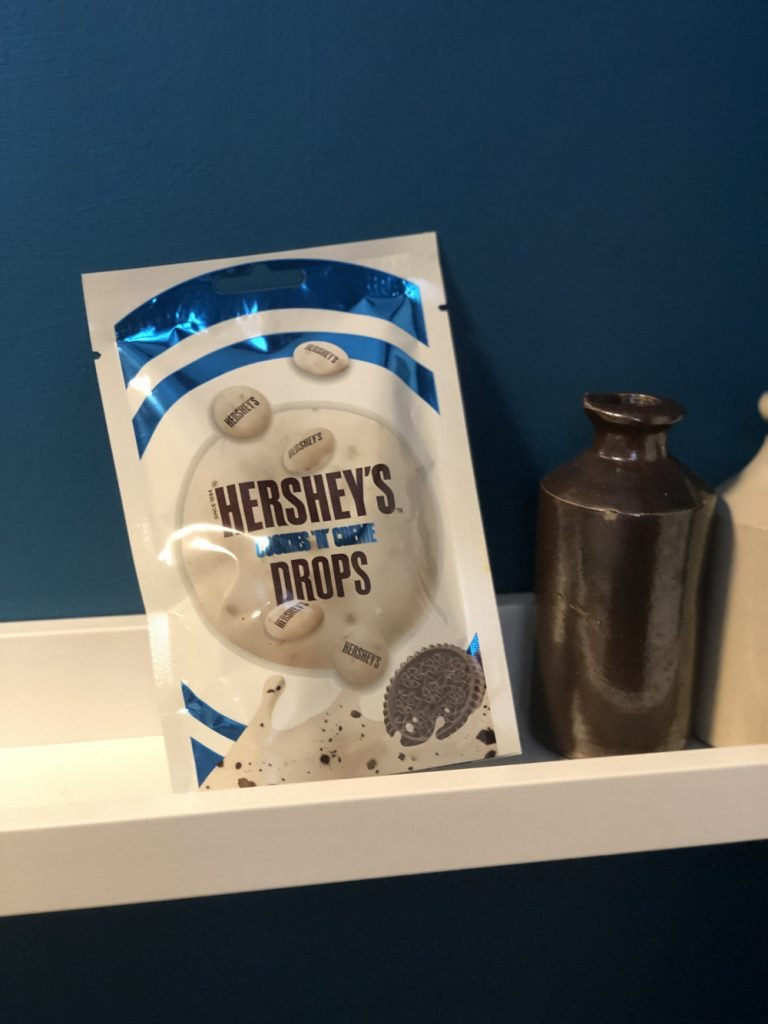 packet of Hershey's drops on a white shelf against a dark blue wall