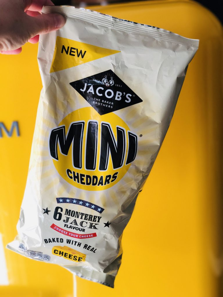multipack of mini cheddars monterey jack flavour being held up in front of a yellows smeg fridge