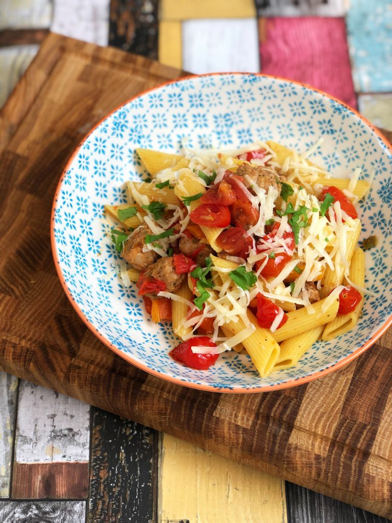 spicy sausage pasta with roast peppers and tomato sauce - sprinkled with cheese, served in blue floral pasta bowl.