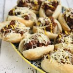 plate filled with chilli cheese dogs - crusty rolls stuffed with real sausages and topped with homemade chilli and cheese