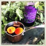 small copper milk pan filled with mulled blackcurrant with clementine slices, cloves, cinnamon and all spice berries.