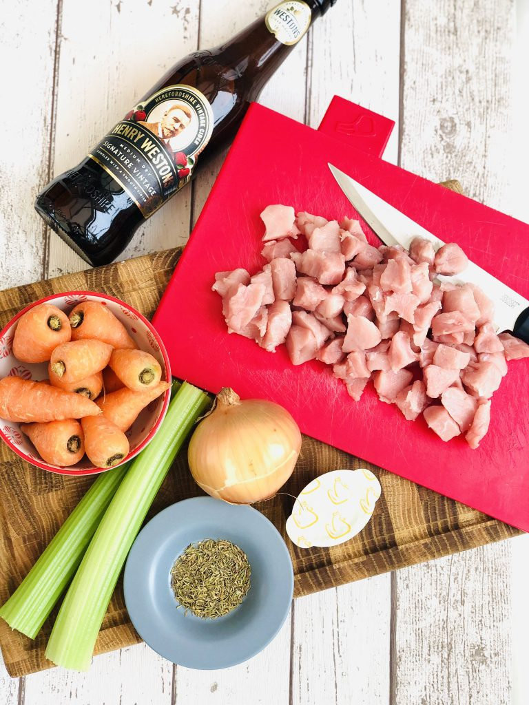 Ingredients for pork and cider casserole - 500g diced pork meat on a red Joesph Joseph chopping board with knife, wooden bowl with 300g baby carrots, 2 sticks celery, one brown onion, one chicken stock pot, 2 tsp dried thyme on a small blue saucer and one bottle of apple cider