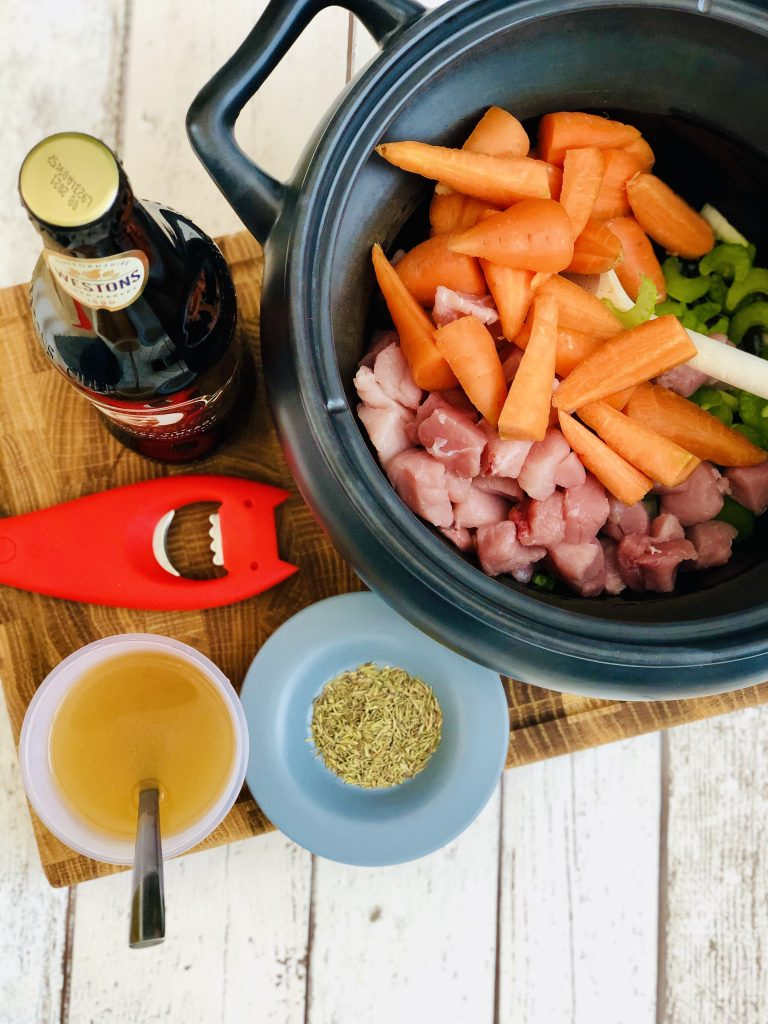 black crockpot slow cooker pan filled with diced onions, sliced celery, diced lean pork and halved baby carrots - the rest of the ingredients for pork and cider casserole are on the table around the pan ready to be added - apple cider with red alessi bottle opener, dried thyme on a pale blue saucer, chicken stock in a plastic measuring cup