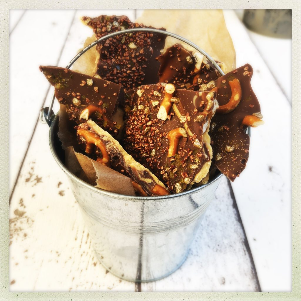 silver bucket of homemade chocolate bark for bonfire night, decorated with salted pretzels, edible glitter, gold and bronze crunch cake toppings