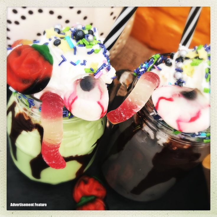 halloween freak shake with green milkshake decorated with cream and jelly sweets and sprinkles