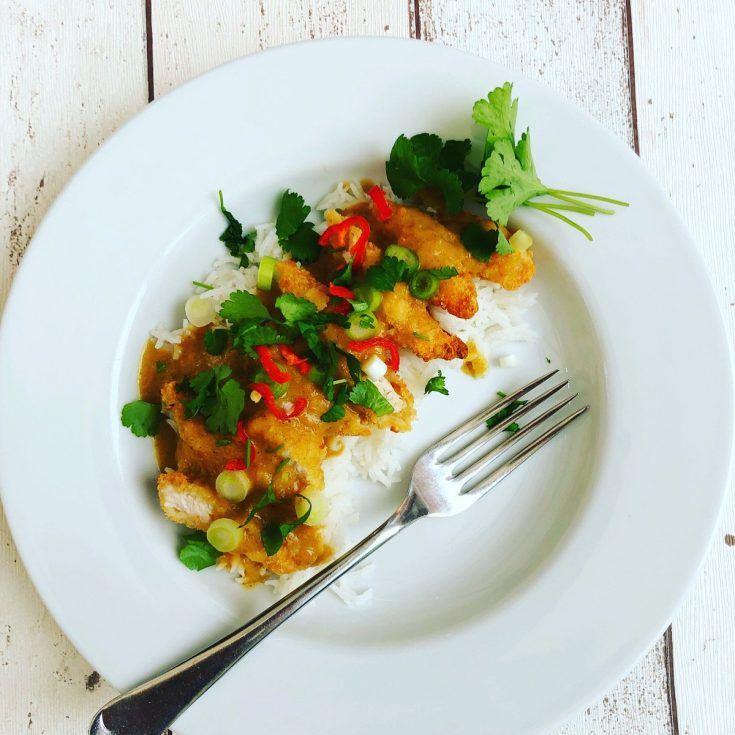 quick chicken curry with crispy chicken strips and peanut butter curry sauce served over rice, garnished with chillies and coriander