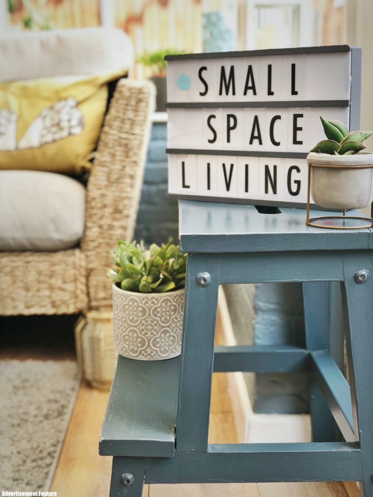 "small conservatory with wicker sofa, grey side table with light box with ""small space living"" written on it. Small plants and lanterns dotted around the room"