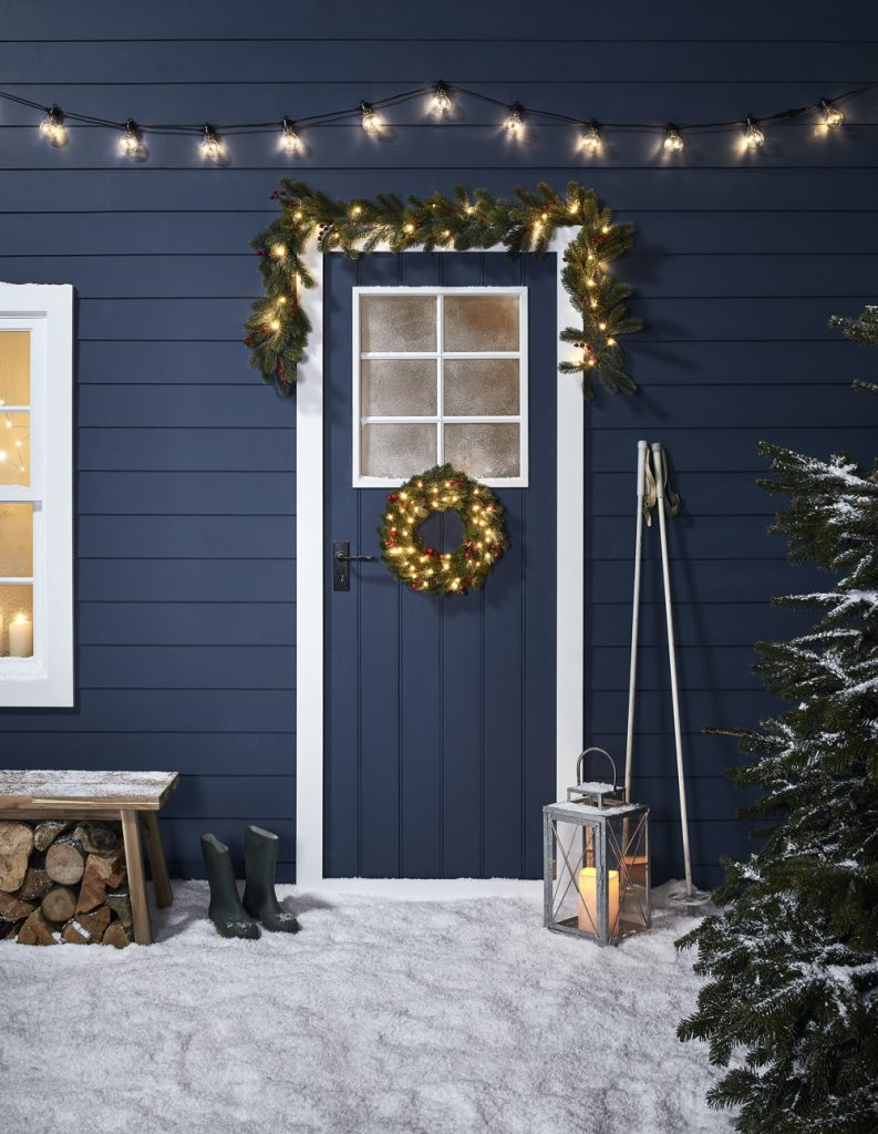 midnight blue cabin with garland and lights decorating the doorway