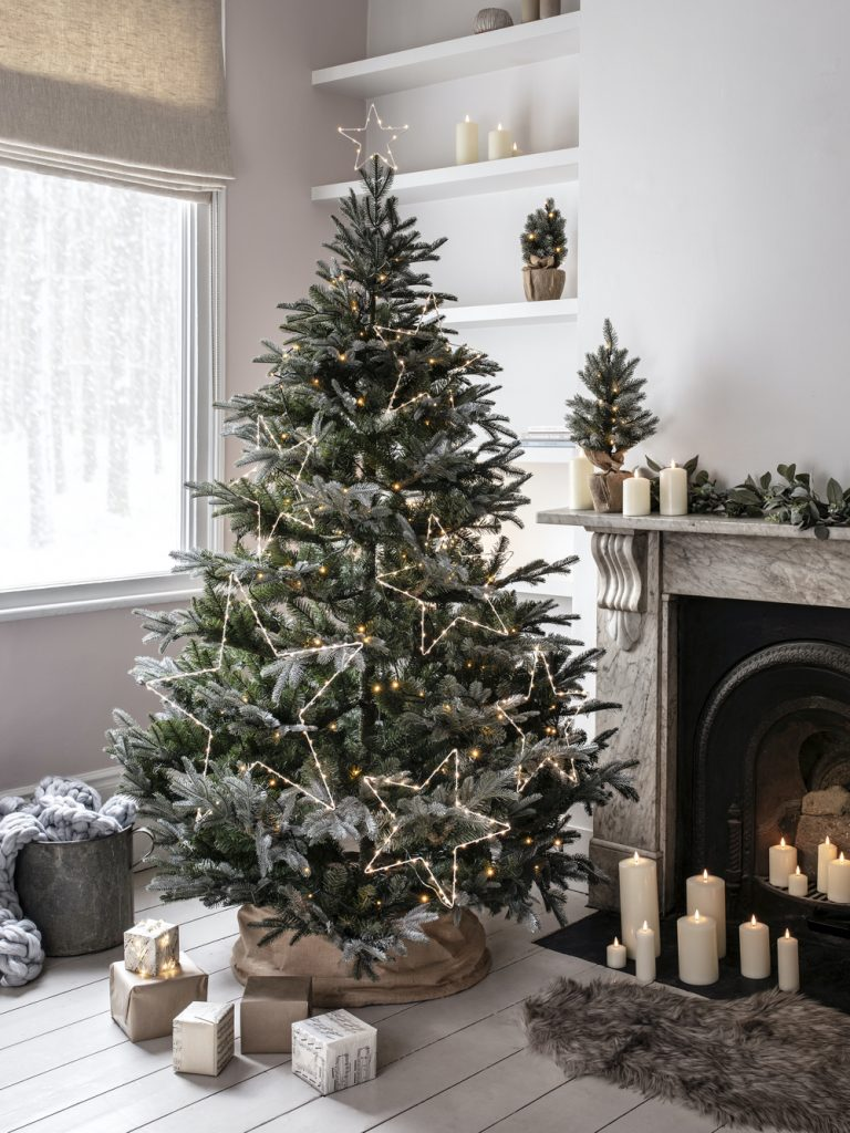 christmas tree decorated with lit up star lights , fireplace and candles in background