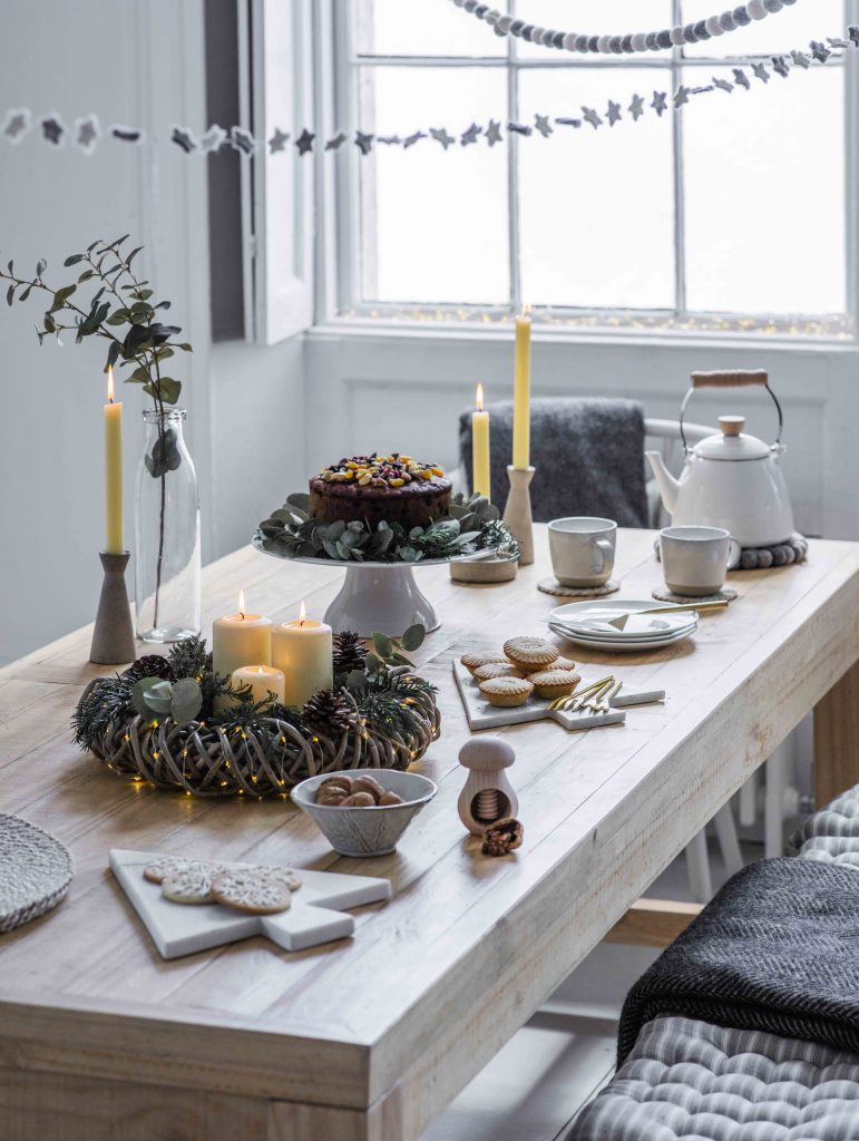 Garden Trading AW19 nordic nibbles collection - wooden table set with christmas tree shaped plate, wreath and candles for decoration along with a white tea set and cake stand holding a fruit cake