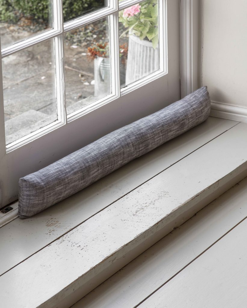 Garden Trading draught excluder in black and white cotton in front of a wooden and glass paned door.